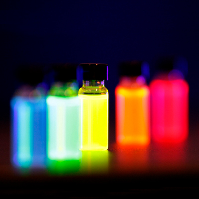 Photo of five small bottles of liquid, glowing red, orange, yellow, green, and blue against a black background.