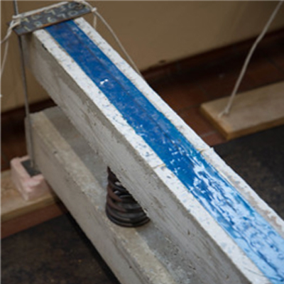 Photo of one long, narrow white concrete bar stacked on top of another, with a thick spring in between. The top bar is filled with a stripe of blue material down the middle.